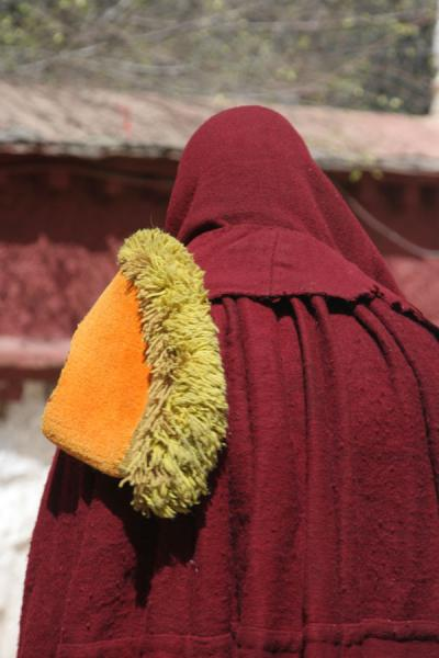 Monk with yellow hat over his shoulder | Sera monastery | China