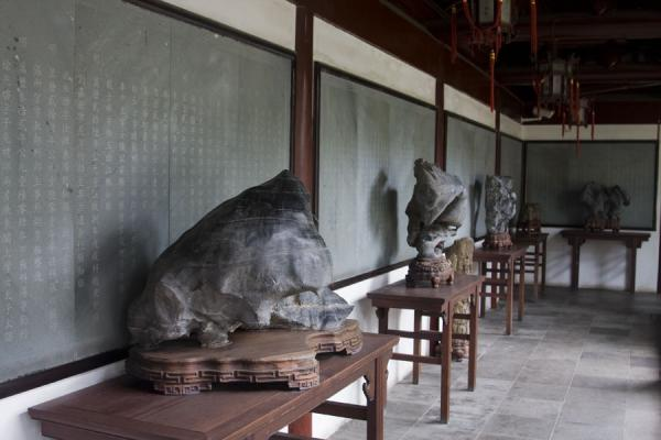 Confucian writings on the wall with curiously shaped stones and pieces of wood in front | Tempio di Confucio | Cina