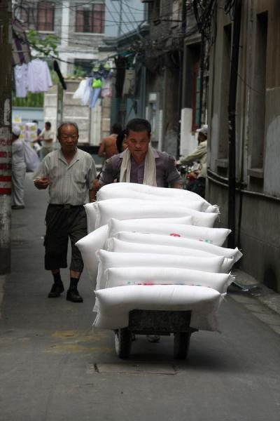 Man walking his wares through one of the narrow lanes | Shanghai | China
