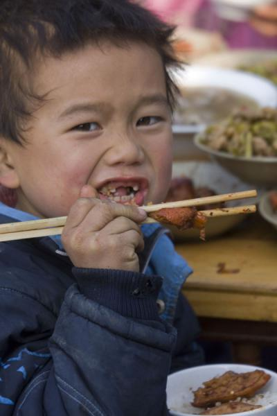 Miao boy eating with chopsticks | Shi Long Zhai | China