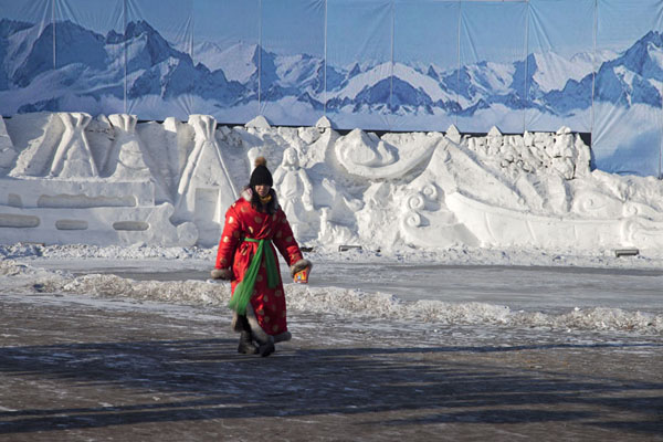 Woman in traditional dress walking on the Songhua river in a snow-sculpted landscape | Songhua Winter Activities | China