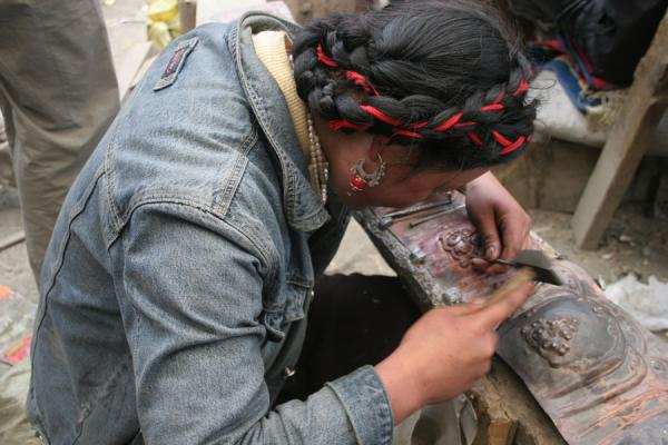 Tibetan girl working hard in the workshop of Tagong monastery | Tagong monastery | China