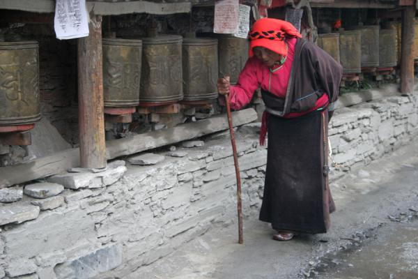 Old woman with cane walking around Tagong monastery | Tagong monastery | China