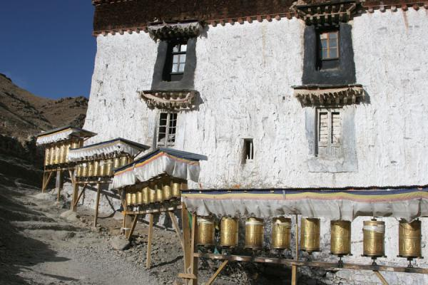 Prayer wheels and building on the way up Tashilhunpo kora | Tashilhunpo kora | China