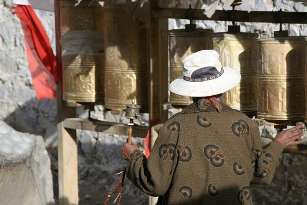 Pilgrim setting the prayer wheels in motion on Tashilhunpo kora | Tashilhunpo kora | China