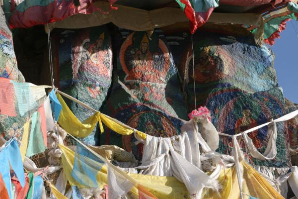 Prayer flags decorating colourful rockpaintings on Tashilhunpo kora | Tashilhunpo kora | China