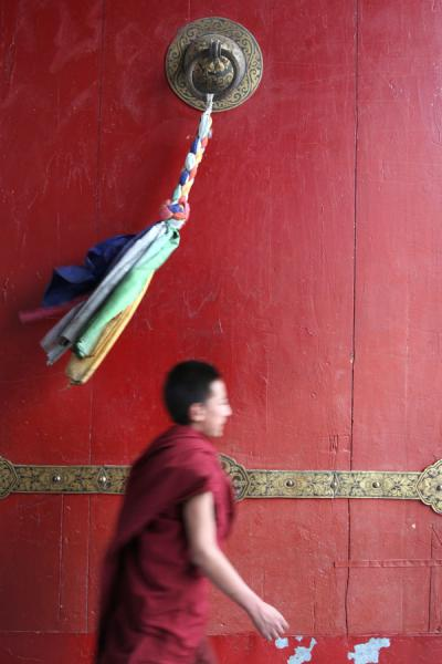 Photo de Tashilhunpo monk walking through one of the massive red doorsShigatse - Chine