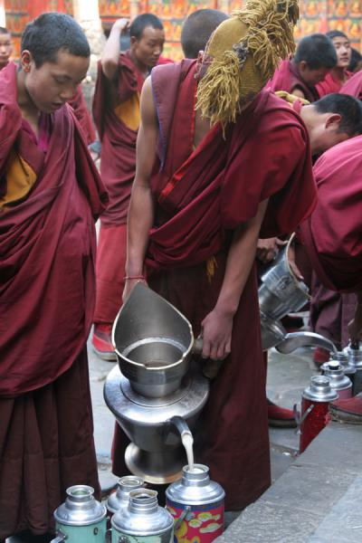 Photo de Monk pouring sweet milk tea in a flaskShigatse - Chine