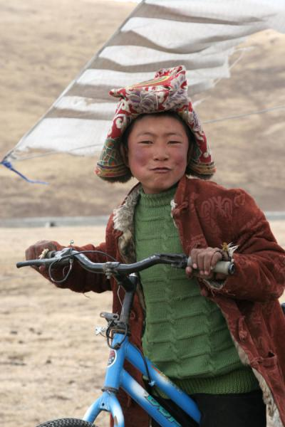 Boy of Tibetan nomads playing on his bike | Tibetaanse nomaden | China