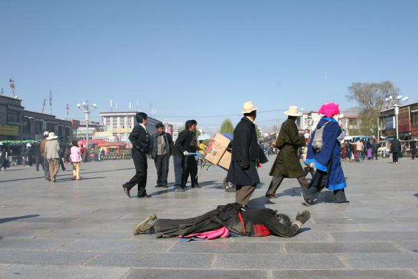 Tibetan pilgrim on Barkhor square, prostrating | Tibetan pilgrims | China