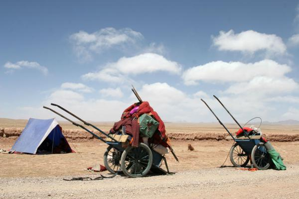 Carts with personal belongings, a tent and a dog in empty Tibetan landscape of Qinghai | Tibetan pilgrims | China