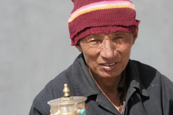 Tibetan pilgrim turning his prayer wheel in Dondrubling monastery | Tibetan pilgrims | China