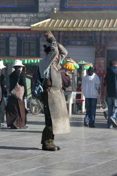 Devout Tibetan buddhist with protective cover prostrating in front of Jokhang temple | Tibetan pilgrims | China