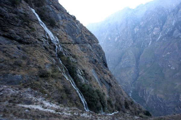 Waterfall cutting through the mountain and trail | Tiger Leaping Gorge | China