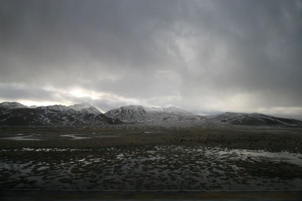 Picture of Train to Lhasa (China): Typical empty, snowy landscape with clouds seen from the train to Lhasa