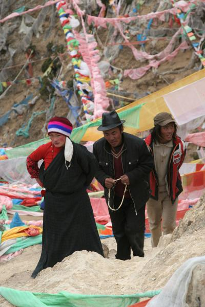 Tibetan pilgrims walking up the hill on their kora behind Wencheng temple | Wencheng temple | China