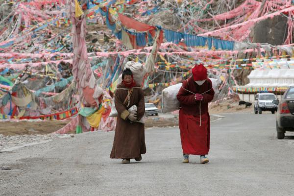 Picture of Wencheng temple (China): Tibetan pilgrims carrying a load near Wencheng temple
