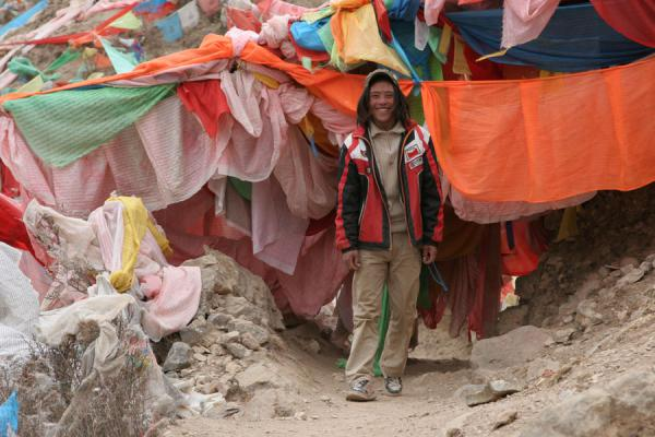 Coming out of a bundle of prayer flags on the kora around Wencheng temple | Wencheng temple | China