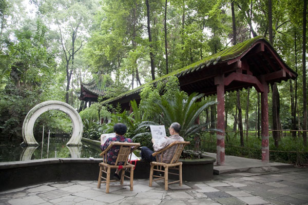 Picture of Old couple sitting at a small pond in the park of the monasteryChengdu - China