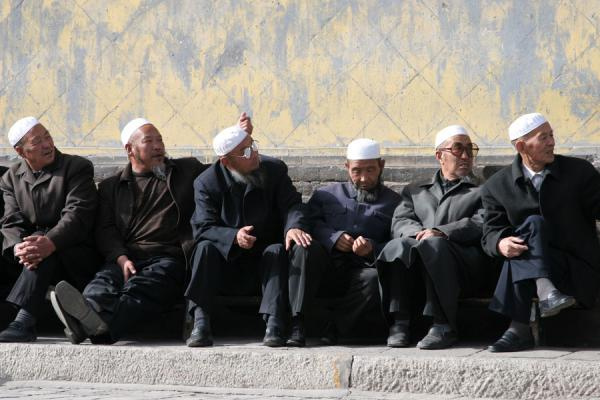 Muslims sitting and chatting in the sun outside the prayer hall of the Great Mosque of Xining | Xining Mosque | China