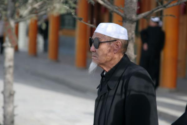 Picture of Xining Mosque (China): Muslim with oversize sunglasses, beard and white hat at the Mosque of Xining
