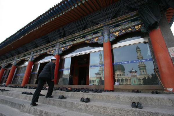 Muslim about to enter the prayer hall with a reflection of the minarets | Xining Mosque | China