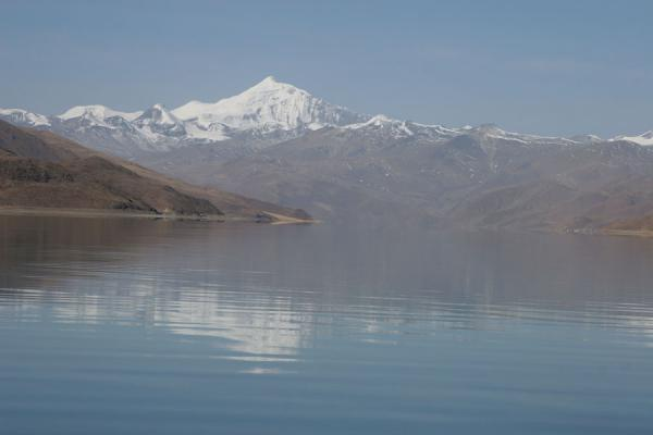 Mount Nojin Kangtsang reflected in the tranquil waters of Yamdrok Tso | Yamdrok Lake | China