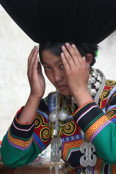Picture of Yi woman in brilliant coloured dress and enormous black hat
