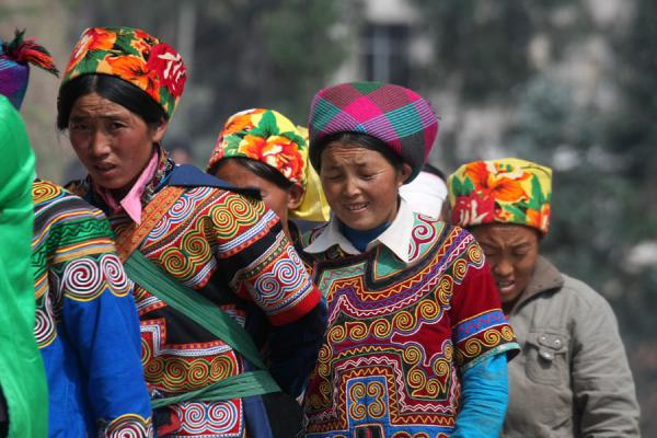 Foto van Yi women in their colourful dresses and hatsPuge - China