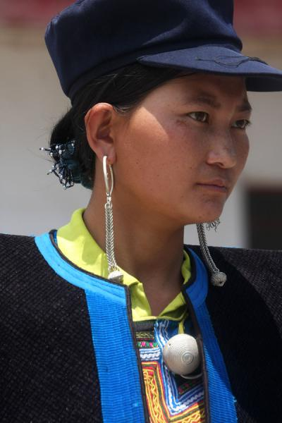 Picture of Yi women (China): Yi woman with cap, cape, and long earrings