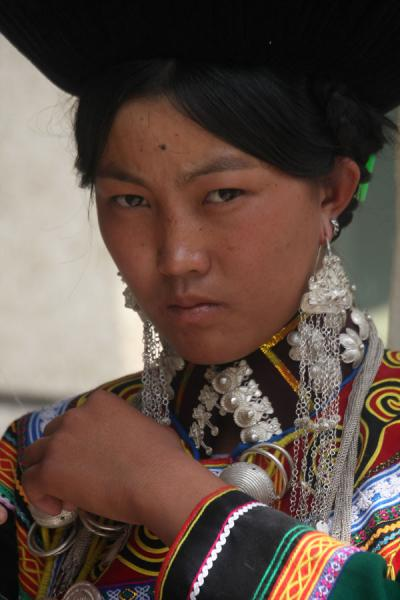 Picture of Yi women (China): Yi woman stares while adjusting her dress