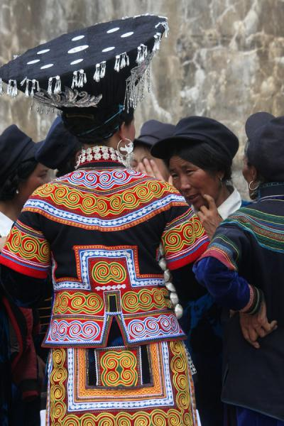 Yi woman with hat talking with other women | Donne Yi | Cina
