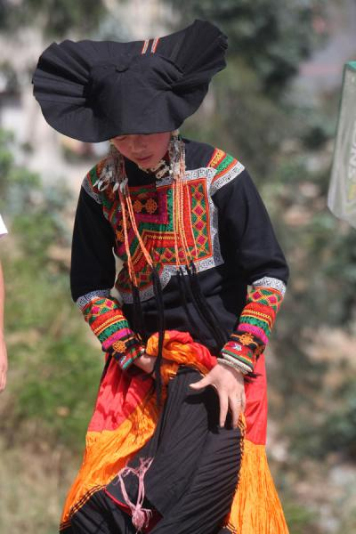 Picture of Yi women (China): Yi woman dressed up in black, orange and red
