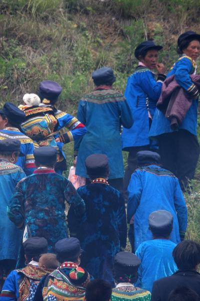 Picture of Yi women (China): Yi women dressed in blue walking up a hill
