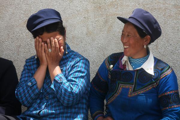 Foto van Yi women in blue dresses having a joyful conversationPuge - China
