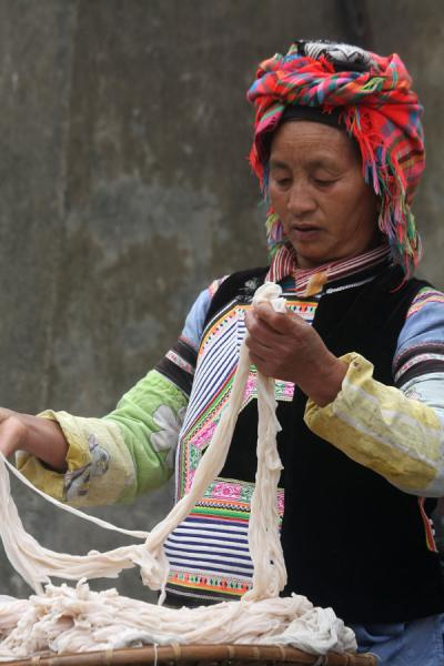 Picture of Yuanyang market people (China): Ethnic woman preparing noodles on the market
