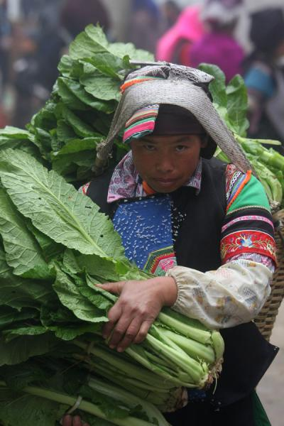 Picture of Yuanyang market people (China): Ethnic woman carrying load of vegetables