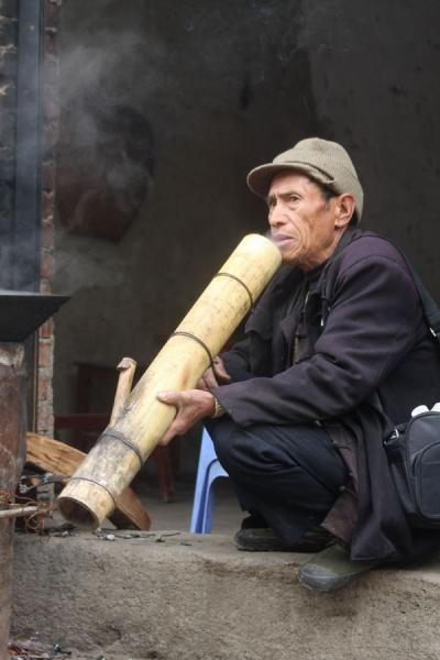 Picture of Ethnic Hani man having a smoke on the market