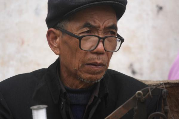 Hani man looking up from his sewing machine | Personas del mercado en Yuanyang | China