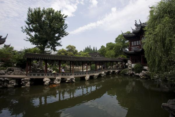 Zig-zag bridge over a pool with pavilion in the background in Yuyuan Garden | Yuyuan Garden | China