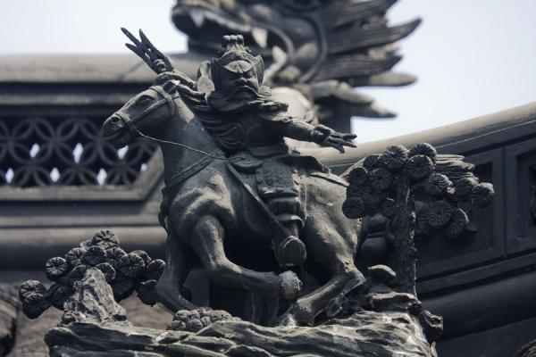 Detail of a sculpted warrior on the roof of one of the pavilions in Yuyuan Garden | Yuyuan Garden | China