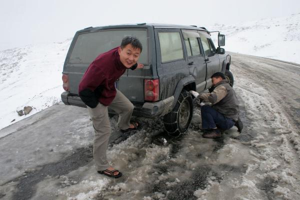 Picture of Zheduo pass (China): Guide warming his feet using the exhaust pipe of the jeep