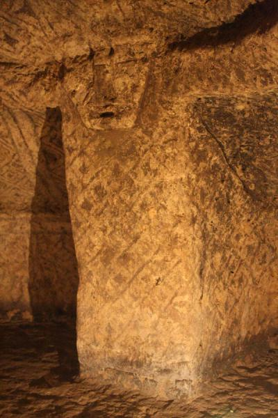 Column with face and decorated wall inside a tomb of Alto de Segovia | Alto de Segovia tombs | Colombia