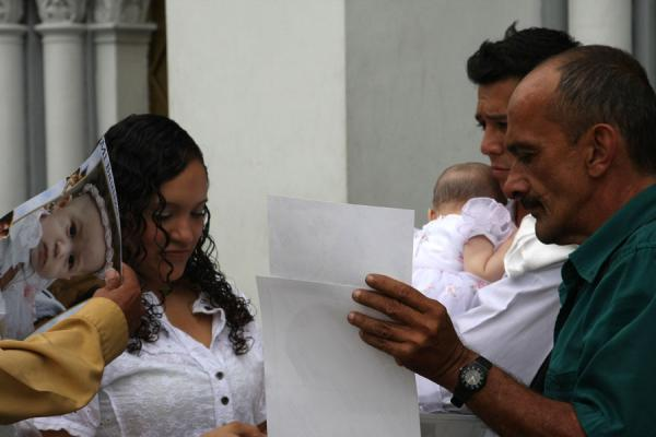 Colombian family looking at the pictures of their baptized child | Colombian people | Colombia