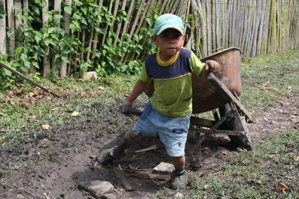 Small boy trying to get a wheelbarrow up a hill | Colombian people | Colombia