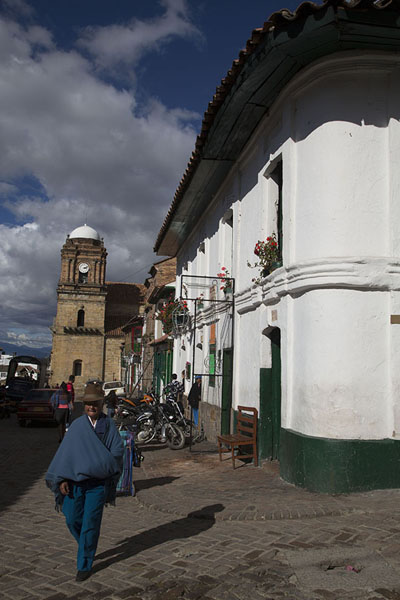 Woman in poncho walking a street in Monguí with the Basilica in the background | Monguí | 哥伦比亚