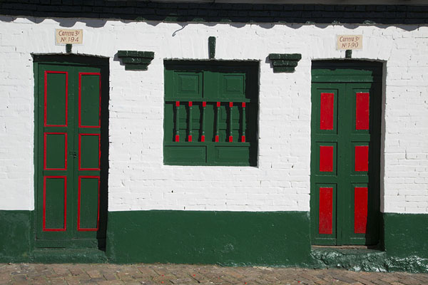 Frontal view of a house with white walls, green and red doors and windows in Monguí | Monguí | Colombia
