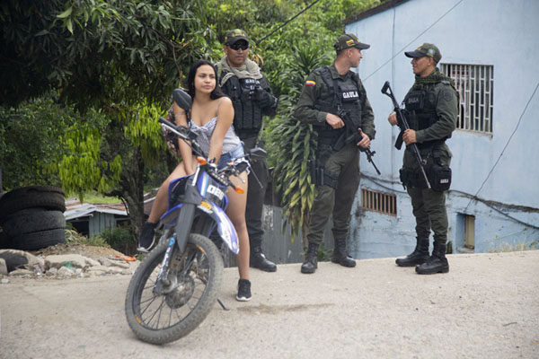 Local girl sitting on a motorbike with army soldiers in the background | Peace road to Marquetalia | Colombia