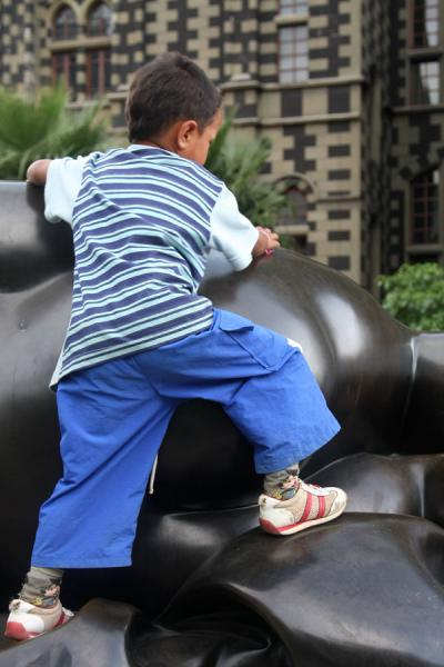 Colombian boy playing on one of the sculptures of a voluptuous woman | Plaza Botero | Colombia