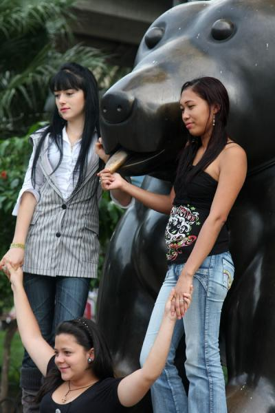 Colombians girls posing at the Dog, one of the animal statues on Botero square | Plaza Botero | Colombia